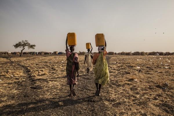 Tres mujeres llevando agua en un campo de desplazados en Melut, Sudán del Sur. || Anna Surinyach