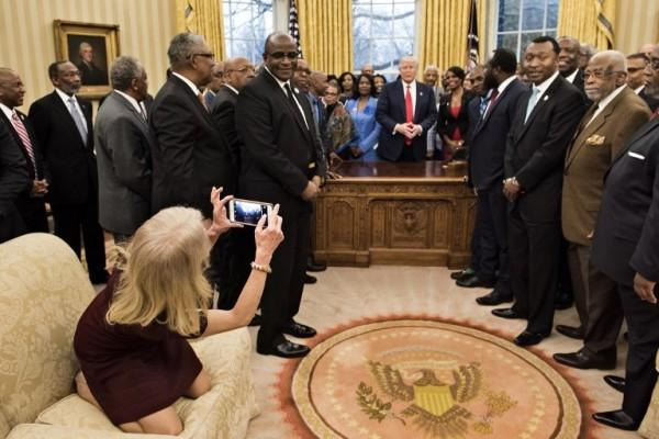 La asesora Kellyanne Conway le toma una foto al presidente Donald Trump || AFP