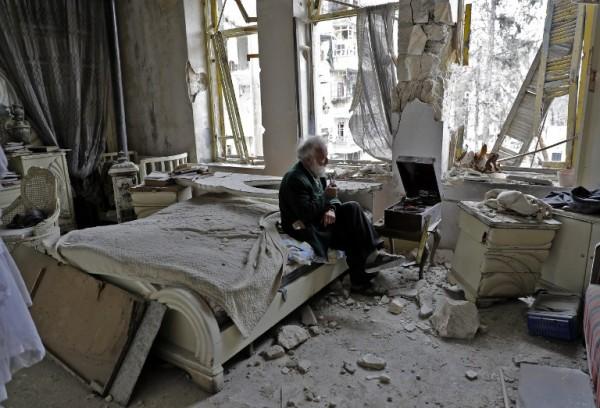 Un anciano sirio fuma y escucha música en su casa destruida || AFP