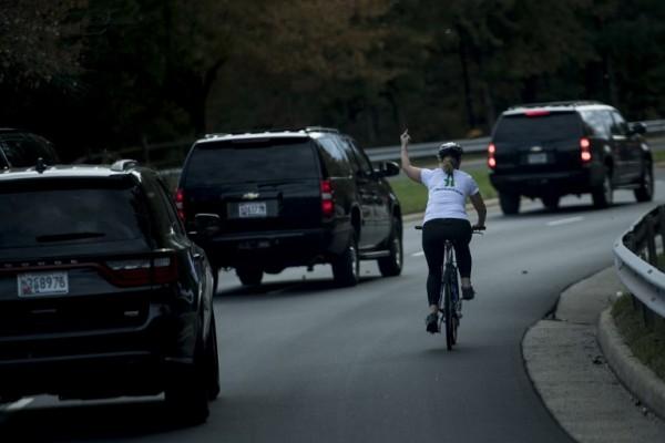 Una mujer realiza un gesto ofensivo hacia la camioneta que traslada a Donald Trump || AFP