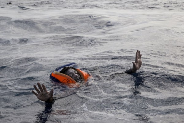 Un migrante a punto de ser rescatado en la costa de Libia || AFP
